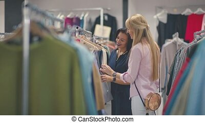 Two beautiful women friends at the store with clothes. -...