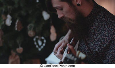 Hipster playing electric guitar. - Hipster with beard,...