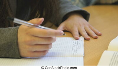 Schoolgirl sitting at the school desk holds a pen - The...