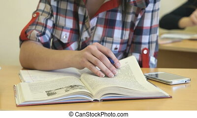 Girl sitting at desk flipping pages of textbook - The girl...