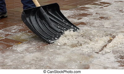 Footage man cleans snow from the yard shovel.