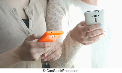 Two girls watching the photos using smartphones - Two girls...