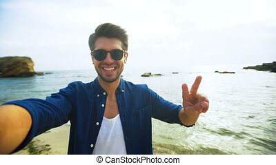 Young handsome smiling man showing his tongue on a camera, while taking selfies on the beach.