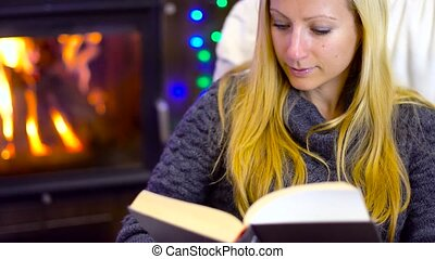 young woman reading book at christmas time