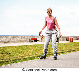 Active young woman rollerskating outdoor. - Active young...