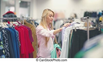 Smiling young woman choosing clothes in a clothing store. -...