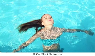 young happy woman swimming and whirls in a swimming pool.