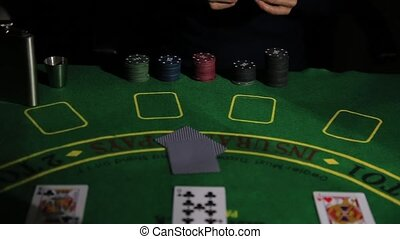 Casino table with poker player hands and playing card. Woman...