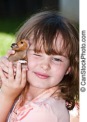 Girl holding her hamster pet close to her face