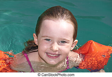 Young girl swimming in a pool in the heat of the summer.