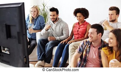 friends drinking beer and watching tv at home - friendship,...