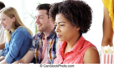 african woman with friends watching tv at home