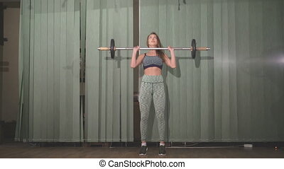 Beautifull girl does attacks with a barbell. 4k