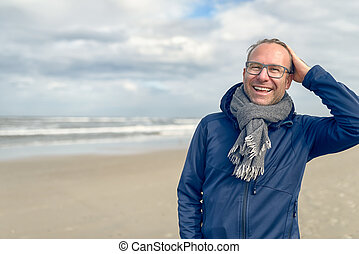Happy middle-aged man on an autumn beach - Happy laughing...