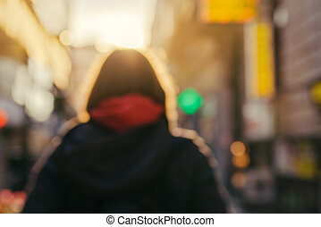 Blur image of unrecognizable female person on the street -...