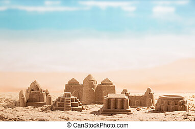 Sand castles, towers and Coliseum on background of sea. -...