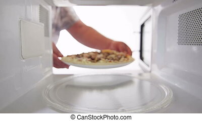 Defrosting frozen seafood pizza in microwave man putting...