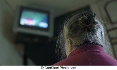 Elderly woman watching television at home small TV mounted on the wall
