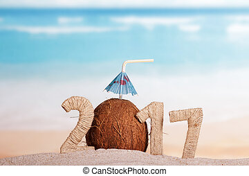 Coconut instead number 0 in 2017 in sand against sea. -...