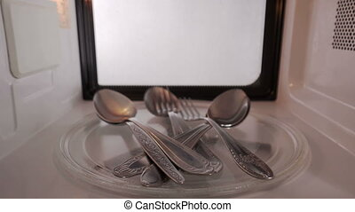 Metal spoons and forks spinning inside microwave oven. Fire...