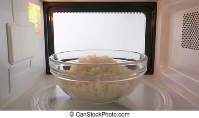 Cooked white rice reheating in the microwave oven inside view