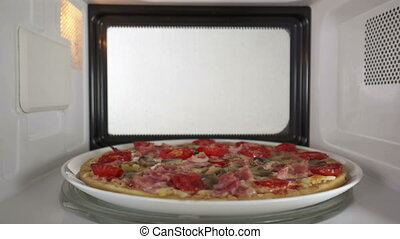 Baked mushroom ham pizza heating in microwave oven inside...