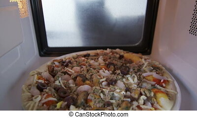 Seafood pizza with shrimp mussels and olives heating in...