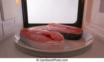 Using microwave oven to defrost salmon steaks before cooking...