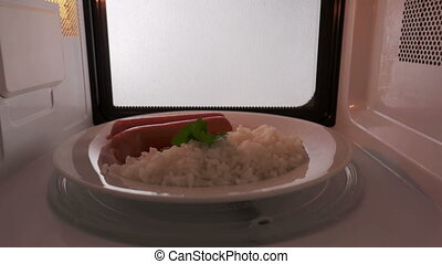 Rice with sausages on a plate heating in the microwave oven...