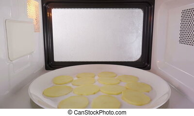Making crispy fat free homemade potato chips in the...
