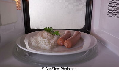 Rice with sausages heating in the microwave oven inside view