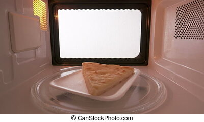 Slice of cheese pie spinning on turntable in the microwave...
