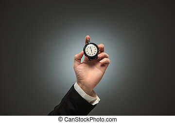 hand holding a stopwatch against a white background - The...