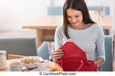 Pretty young woman checking her bag in a cafe.
