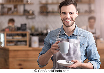 Positive smiling man holding cup of coffee.
