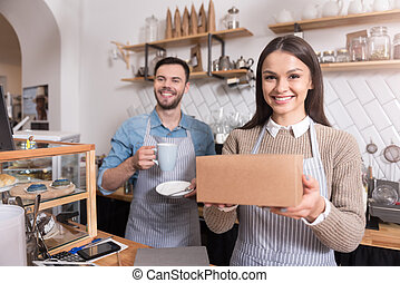 Charming smiling waiters holding cup and box.