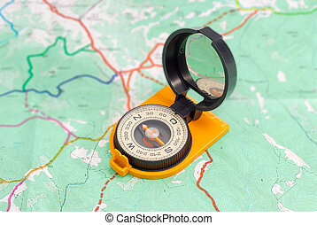 Hand magnetic compass on a tourist topographical map - Dry...
