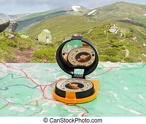 Magnetic compass on tourist map on background of mountain...