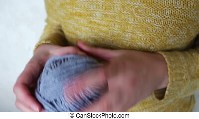 ball of grey wool yarn - female hands hold the yarn a ball...