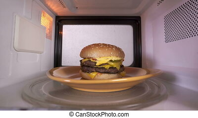 Reheating cooked double cheeseburger hamburger in the...