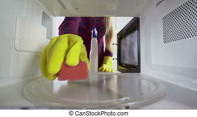 Cleaning microwave girl with sponge and cleaner wiping...