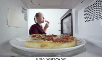 Girl using microwave for reheating food baked pizza on a...