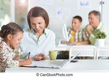 Mother with daughter do homework - Young mother helping her...
