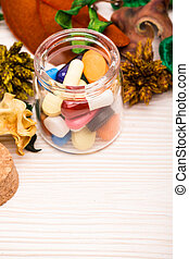 Various pills and capsules in glass container with green