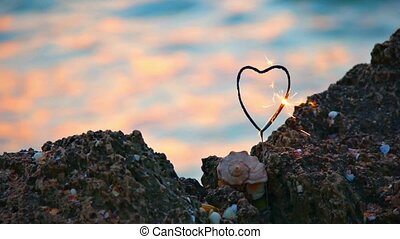 Romance concept. Heart-shaped sparkler and seashell on rocky...