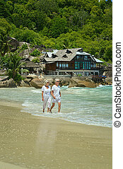 elderly couple running on beach - Happy elderly couple...
