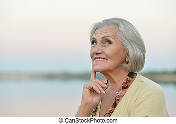 Portrait of a beautiful senior woman on a background of  sky