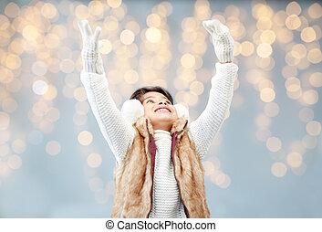 happy little girl wearing earmuffs over lights - winter,...
