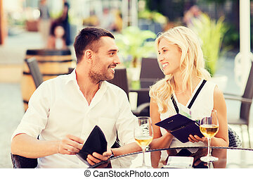 happy couple with wallet paying bill at restaurant - date,...
