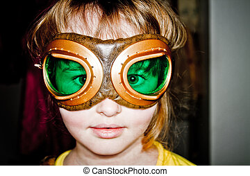 Young girl playing dressup with aviation goggles